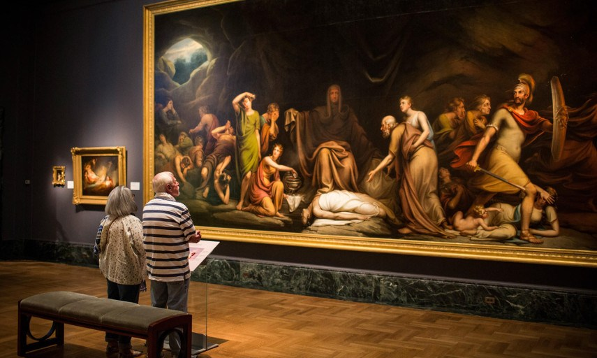 Photo of a man and a wormen looking at a painting at the Detroit Institute of Arts