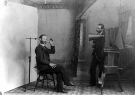 A photographer appears to be photographing himself in a 19th-century photographic studio
