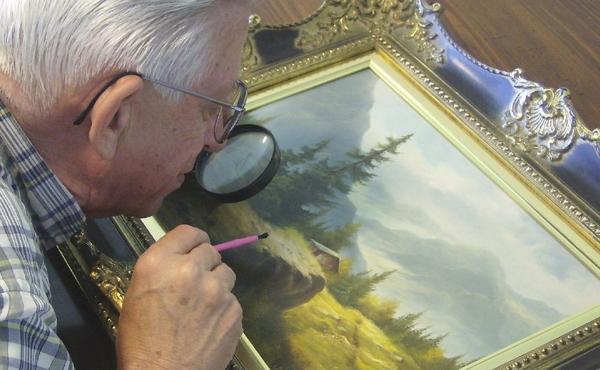 Photo of a man examining a print artwork from up close as he hopes to search for more information on the work