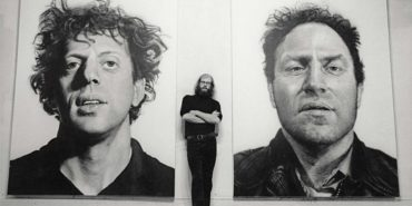 Charles Close - Photo of the artist between his artworks - Image via chuckclose
