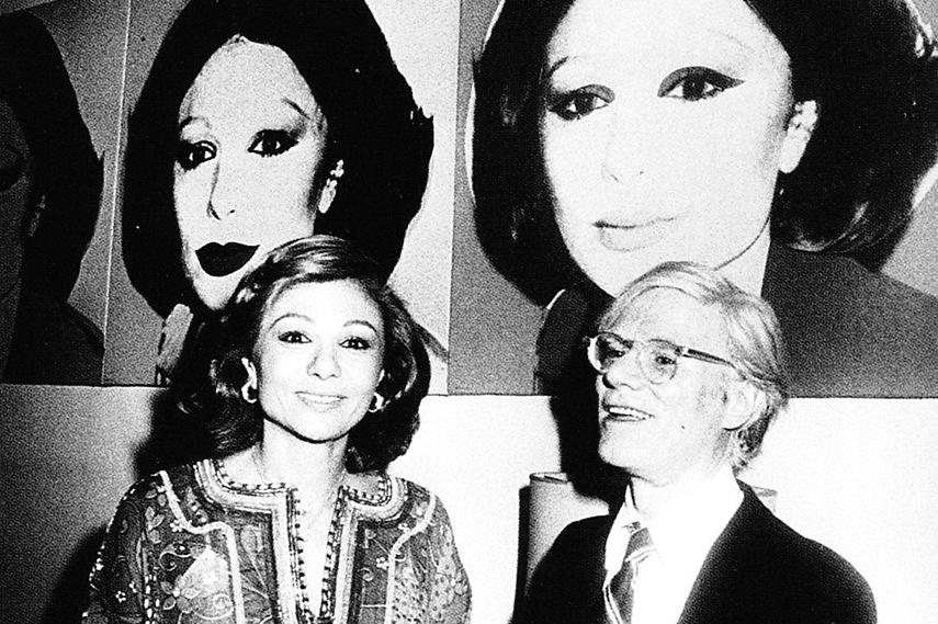Farah Pahlavi with Andy Warhol in 1977 next to her portrait done by the artist. Photo via collectortribune.com