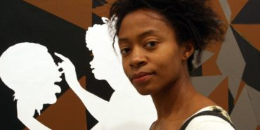 Kara Walker - Photo of the artist in front of her work - Image via Tina Fineberg