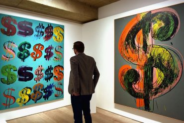 Man Looking at a PIece Made Out of Dollar Signs - Image via insidehookcom