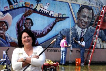 Photo of Judy Baca in front of the wall- Image via archiveli