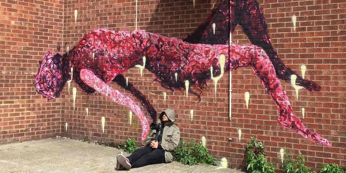 Rafael Sliks -  Artist siting in front of his work - Photo Credits Rafael Sliks