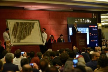 Tehran Auction employees hold a painting from Sohrab Sepehri's Tree Trunk series