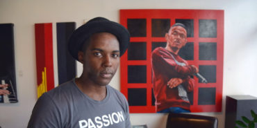 Thomas Evans, aka Detour, stands in front of his portrait of Kendrick Lamar at the Art Gallery at the DPAC - image courtesy of Colorado Public Radio