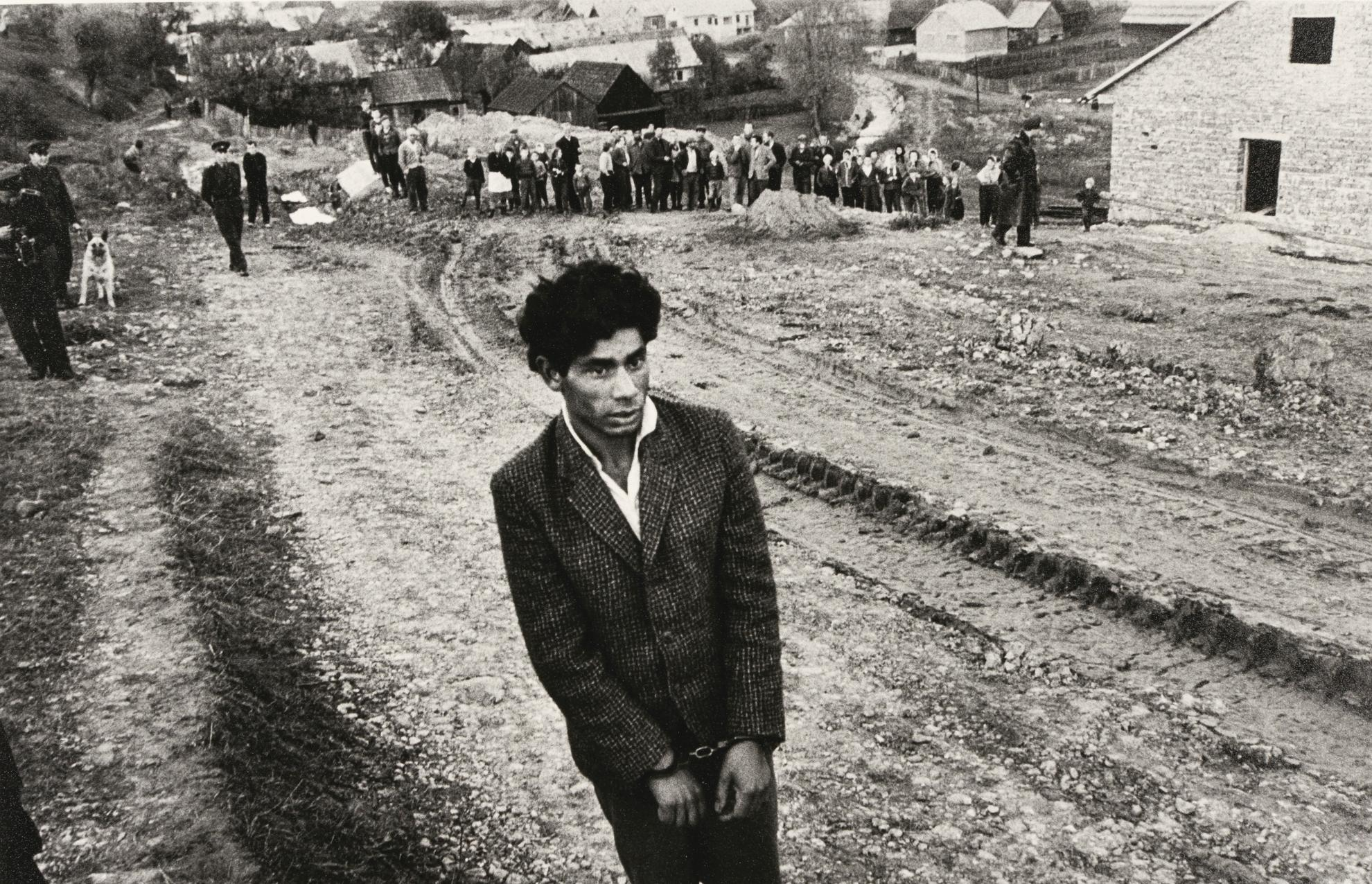 Josef Koudelka-Reconstruction Of A Homicide. In The Foreground: A Young Gipsy Suspected Of Being Guilty, Czechoslovakia, Solvaki, Jarabina-1963