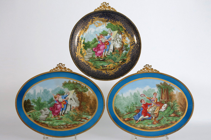 A round and a pair of oval plaquettes in porcelain, with signed paintings, and with guilded mountings-