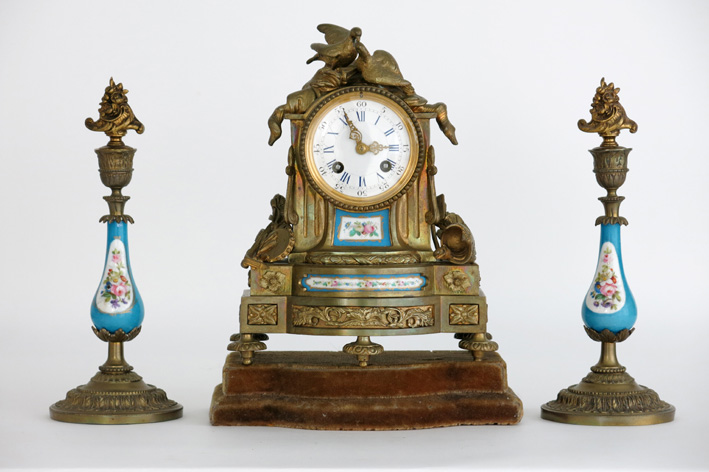19th Cent. French neoclassical garniture in guilded bronze and Sevres-porcelain: a pair of candlesticks and a clock-