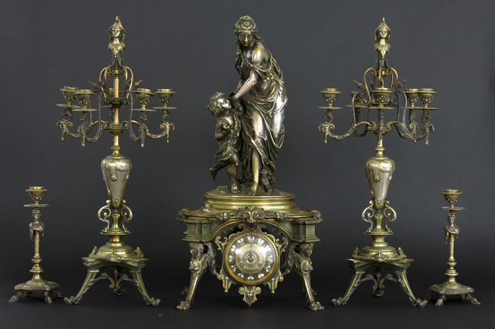 19th Cent. French neoclassical garniture in bronze with a pair of candelabras, a pair of candlesticks and a quite special clock with a sculpture-1870