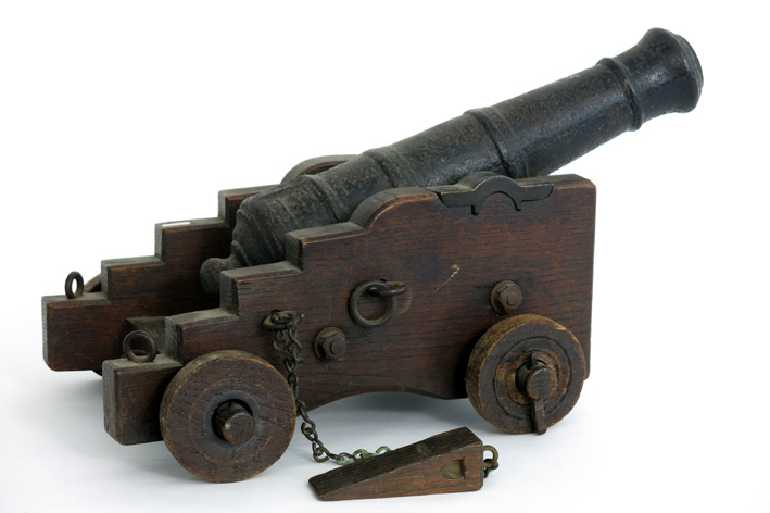 Antique miniature cannon in bronze on stand in wood-