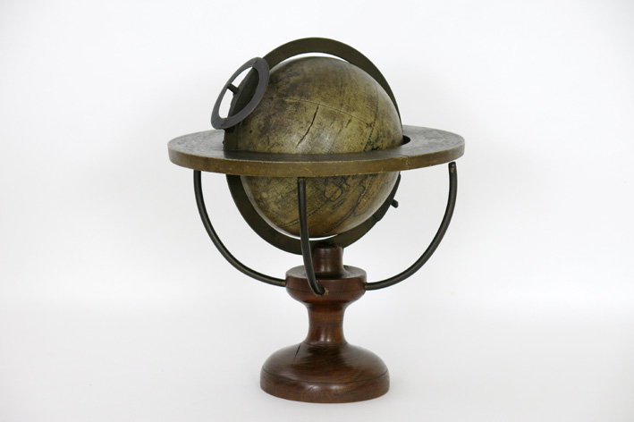 Antique earth globe with brass ring and meridian on/in a wooden stand-