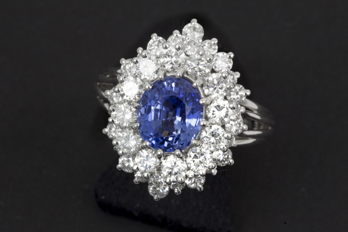 Classic ring in white gold (18 carat) with an oval Siamese sapphire of ca 2,90 carat and ca 2,30 carat of high quality brilliant-