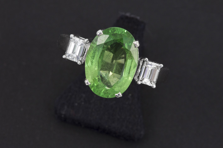 Ring in white gold (18 carats) with a tsavarite of ca 4 carat with very nice color, flanked on both sides by an emerald-cut diamond, together weighing 0,42 carats-