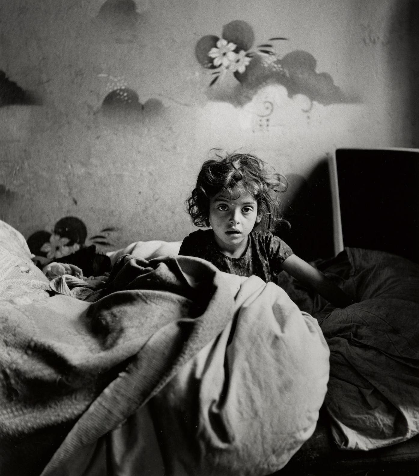Roman Vishniac-Sara, Sitting In Bed In A Basement Dwelling, With Stenciled Flowers Above Her Head, Warsaw-1937