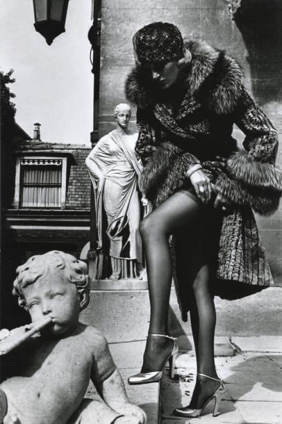 Helmut Newton-Woman in Fur coat adjustint stocking, Paris, Vogue-1975