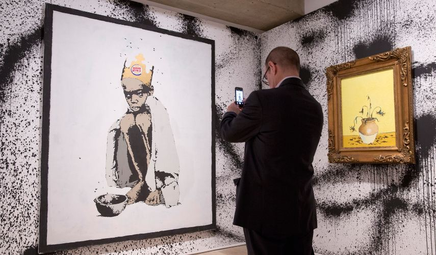 Photograph of a man taking a picture of an artwork - If you work in the art financial world, investing new price into new markets can be a good way to build your business and advance careers