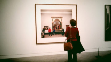 A photo of a woman looking at a photo of people looking at paintings. Taken at the Tate Modern using the Vignette app on my mobile phone.