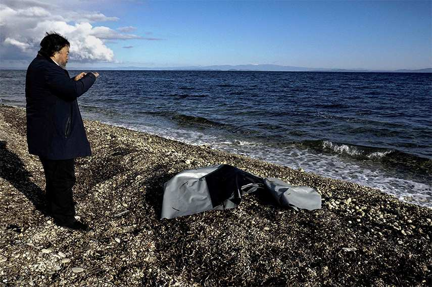 Ai Weiwei takes a picture of the remains of a rubber boat