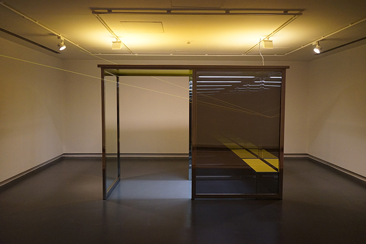 Angela Bulloch - Vanishing Waiting Room, 2008. 6 polished stainless steel tubes, 2 one-way mirrors and 2 two-way mirrors, yellow MDF roof, yellow bench, Lamps with cross dimming program, yellow electroluminescent wire, 300 x 120 x 250 cm. Installation view 2016: Sharjah Art Museum. Courtesy Esther Schipper, Berlin. Photo by Wladimir Tschirsky