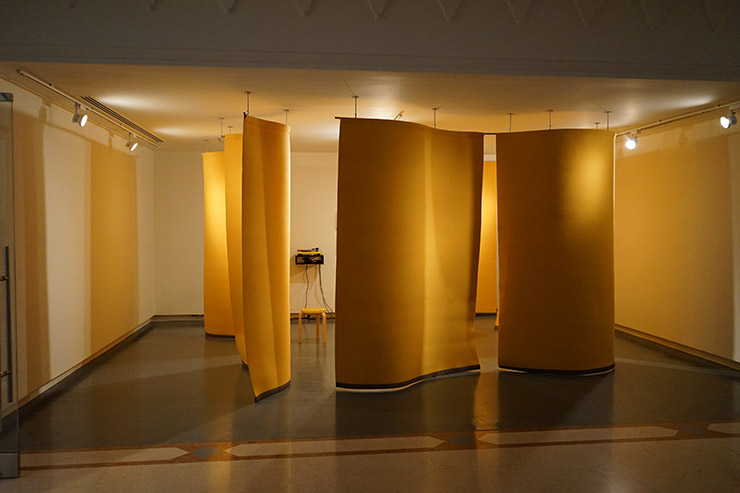 Angela Bulloch - Yellow Music Station - Extra Large, 2012. 6 yellow felt curtains, yellow Alto Alvo Stool 60, Yellow record player, Genelec Speakers, ABCDLP records, Variable Dimensions, Curtains are 180 cm wide each. Installation view 2016: Sharjah Art Museum. Courtesy Esther Schipper, Berlin. Photo by Wladimir Tschirsky