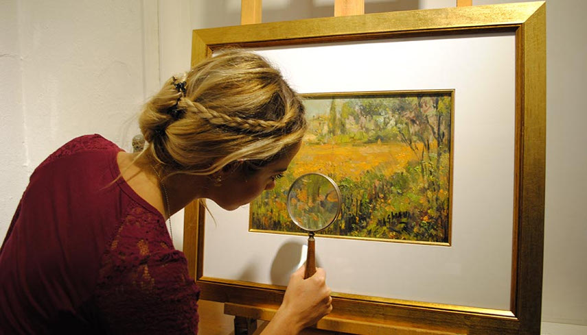 Photo of an appraiser taking a closer look at the painting, determining it's sales information and use
