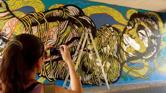 Bastardilla - Photo of the artist in front of her work - Photo Credits Street Art News