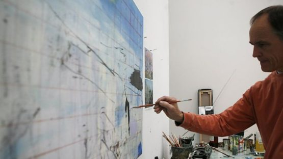Christopher Brown works on a painting in his studio, photo credits - SF Gate