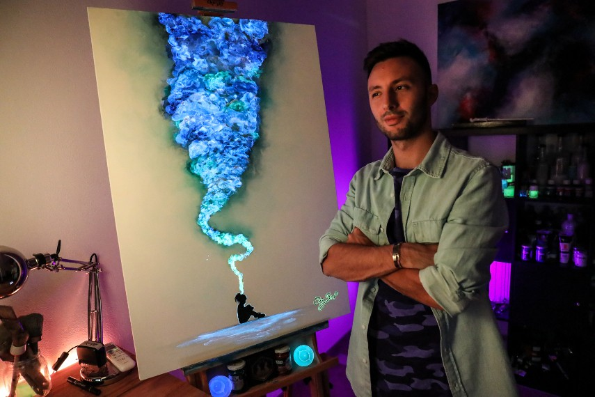 Photo of the artist in front of his painting, presenting the art that can glow in dark due to paint availabe to shop on youtube