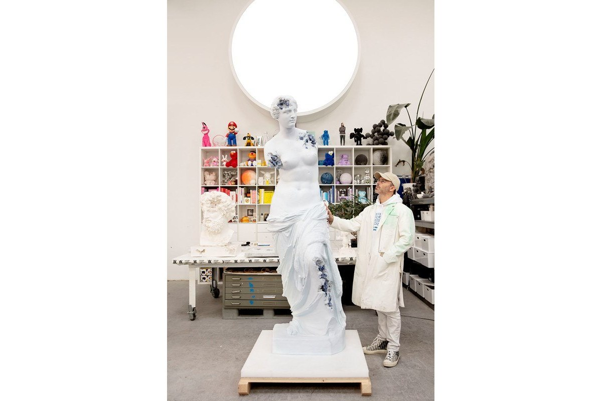 Daniel Arsham standing in front of his sculpture Blue Calcite Eroded Venus of Milo