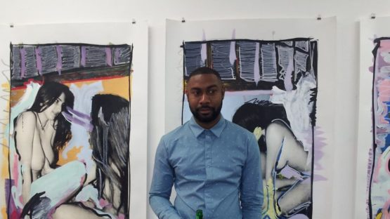 Danny Augustine in front of his works