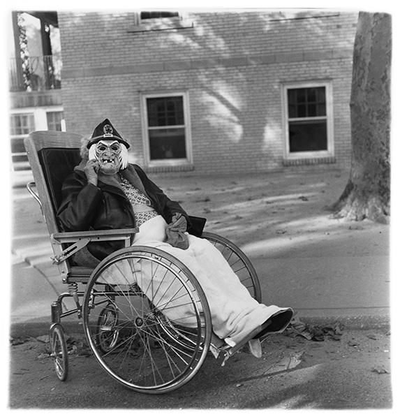 Diane Arbus - Masked woman in a wheelchair, Pa. 1970