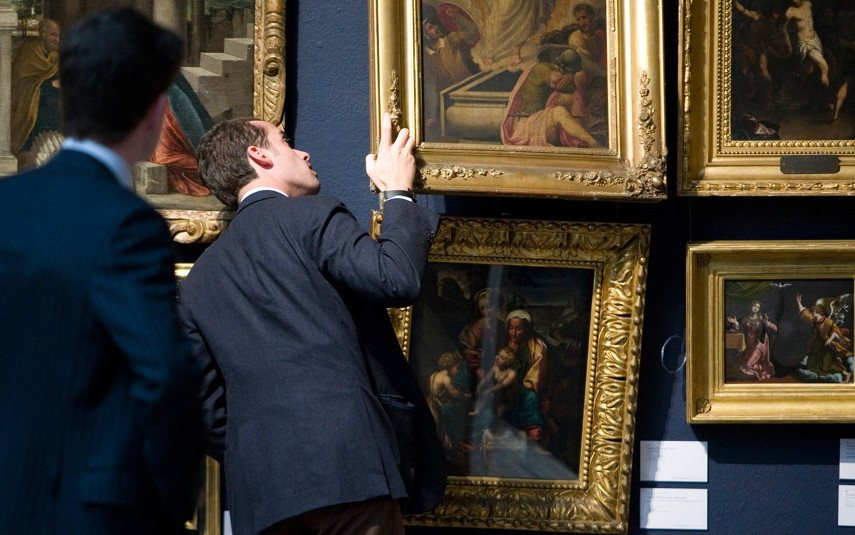 A man taking a look at the condition of a painting in search for additional information with the use of nothing more but his eyes