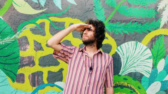 Gola Hundun in front of his mural, photo by Diana Larrea