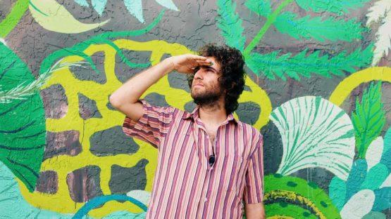 Gola Hundun in front of his mural, photo by Diana Larrea