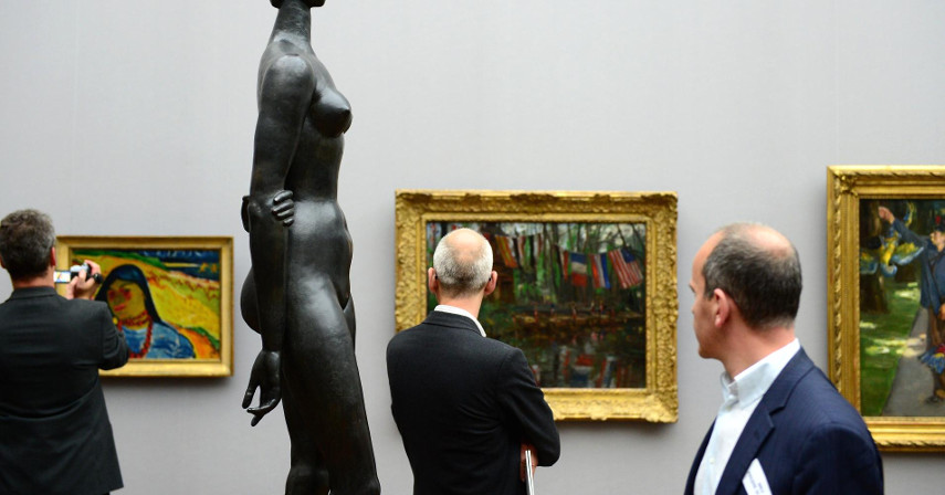 An image of a few potential investors looking at paintings