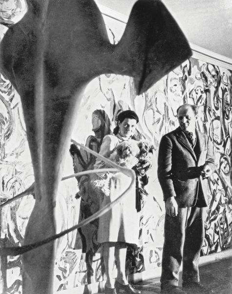 Jackson Pollock (American) and Peggy Guggenheim standing in front of Pollock's Mural