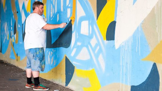 Justus Roe working on his mural under Chicago's Kennedy Expressway, photo © Max Herman