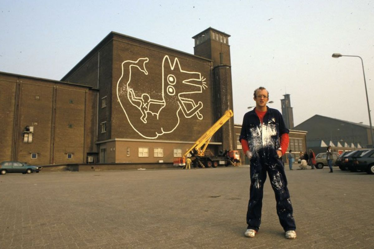 Keith Haring in front of the mural in Amsterdam