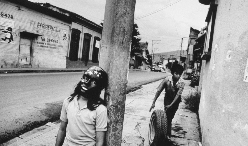 Larry - EL SALVADOR. San Salvador. Child with star mask during Day Of The Dead. Other child in background rolls tire for repair in garage where he works at an adult's job. 1992 (detail), a photo in multiple books