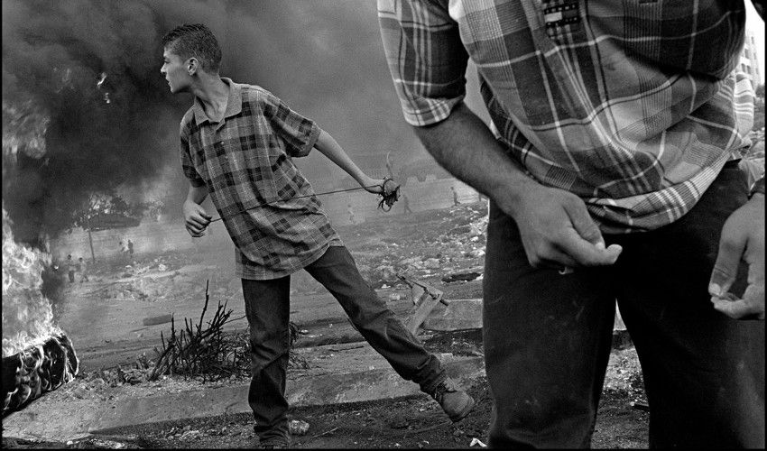 Larry Towell - ISRAEL. Ramallah. West Bank. Palestinian demonstrators in clash with Israeli soldiers. One child has just thrown a rock with a home catapult, 2000 (detail)