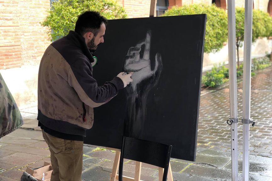 The artist Superstop live painting during the exhibition