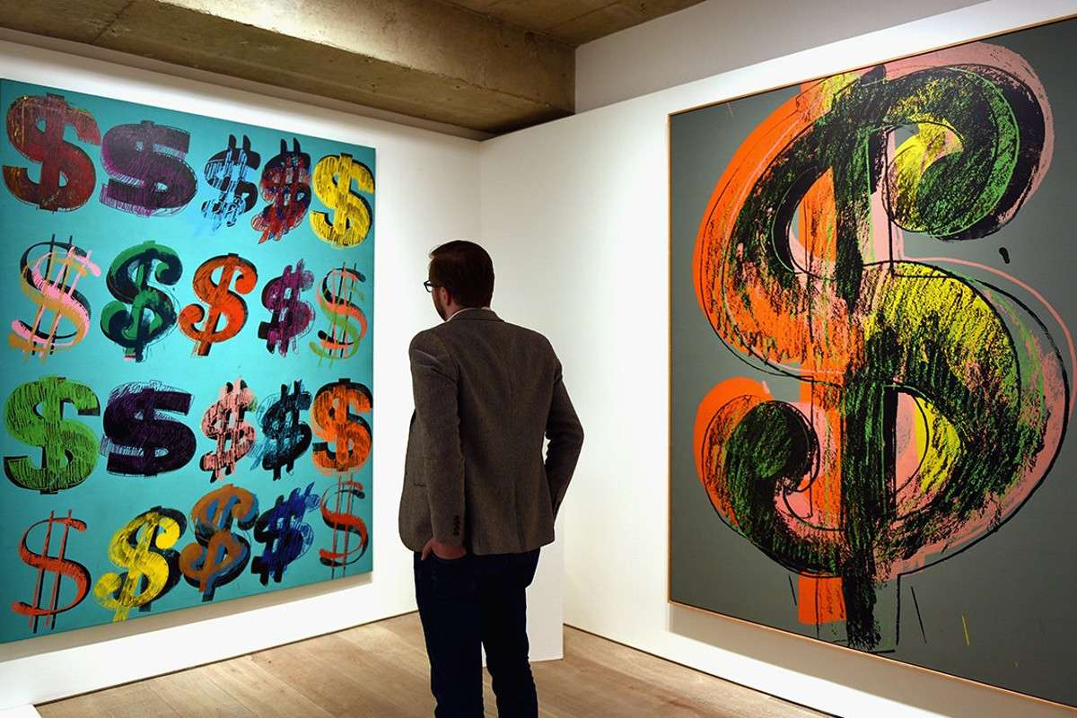 Man Looking at a PIece Made Out of Dollar Signs - Image via insidehookcom view