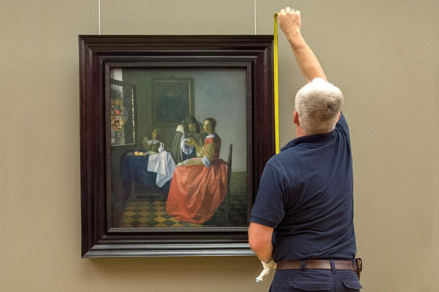 Photo of a man measuring an artwork