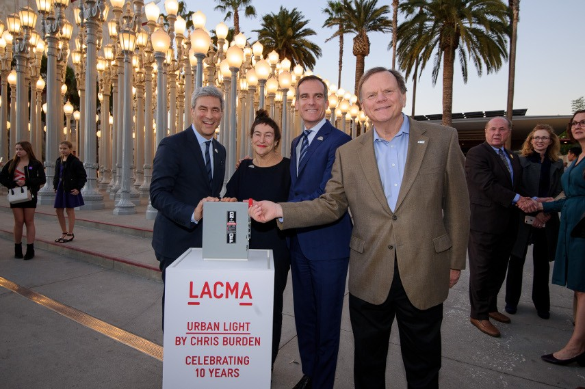 People standing near the sculpture lamps as the lights from home shine in the background of LACMA museum, seeking the best view on the lamps and installation