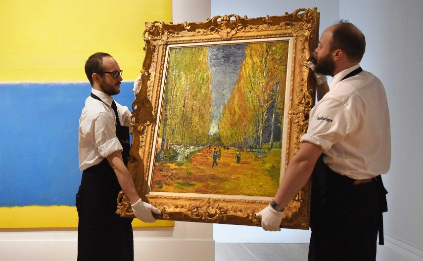 An image of two men moving a painting