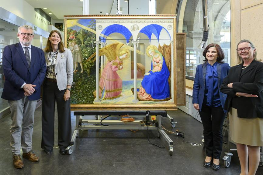 Museum staff and partners next to The Annunciation by Fra Angelico