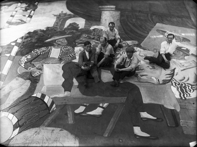 Pablo Picasso and scene painters sitting on the front cloth for Parade
