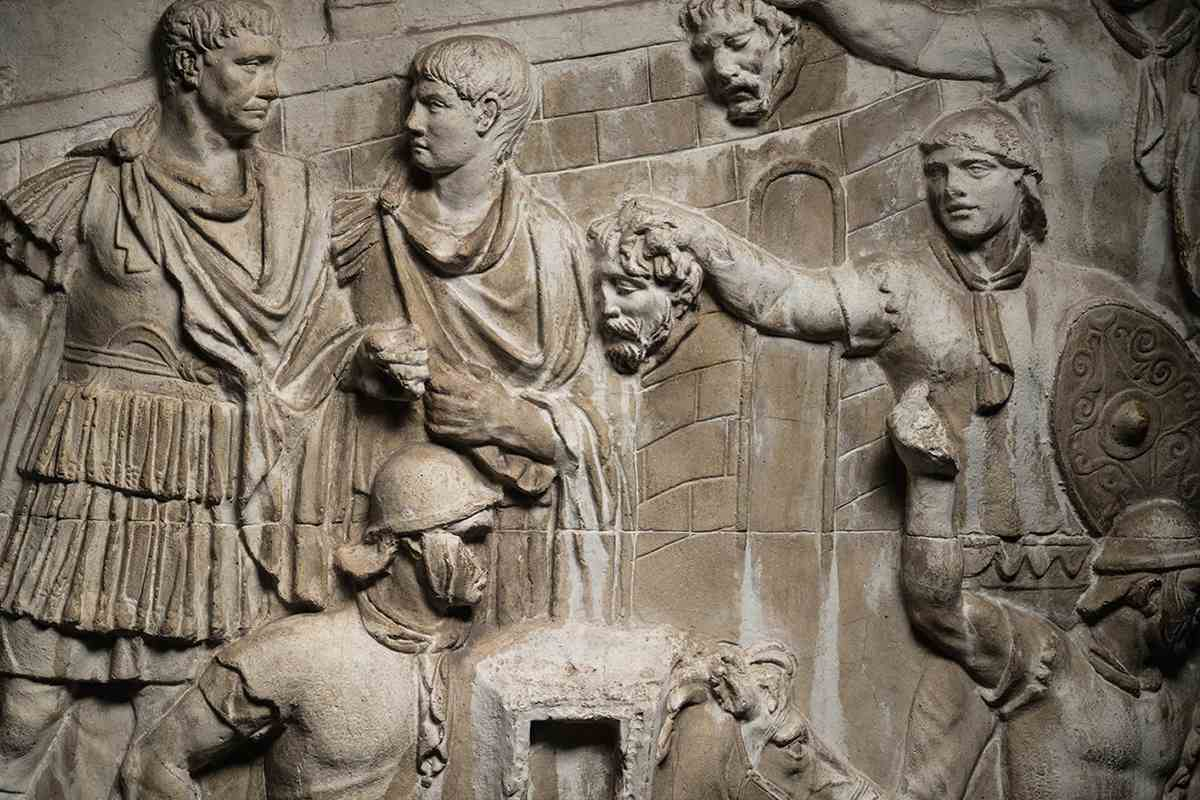 Picture of a scene in the column where two Roman auxiliaries present Trajan with severed enemy
